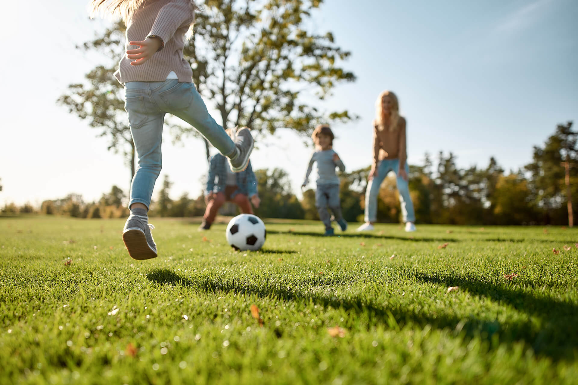 Kids outside playing soccer on a grass field
