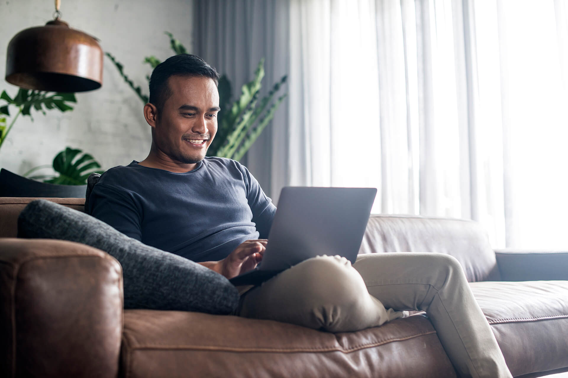 Young adult male relaxing on a couch using his laptop computer