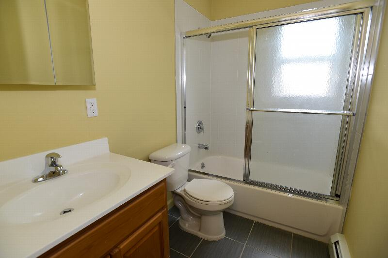 Carteret Gardens bathroom photo shows full size tub wnd shower with glass shower doors. There is a toilet and vanity with sink. A mirrored medicine cabinet is on the wall above the vanity.