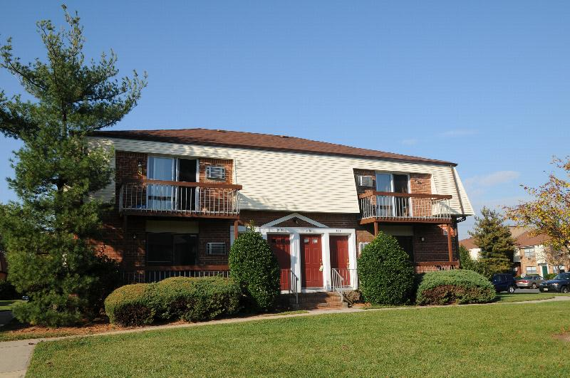 North Brunswick Manor Exterior photo showing a brick exterior and several balconies. Several bushes and trees highlight the landscape.