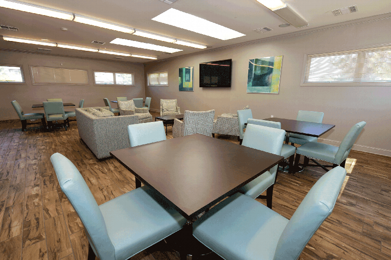 Photo of North Brunswick Manor Clubhouse Community room showing wood grain flooring, multiple seating areas and a large screen TV mounted on the wall.