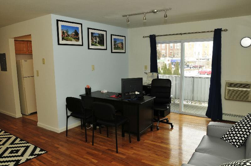 State Fayette Rental Office photo showing a couch, a desk, three chairs and a computer. Hardwood floors run the length of the room. The kitchen can be seen in the background. Sliding glass doors lead to the balcony.