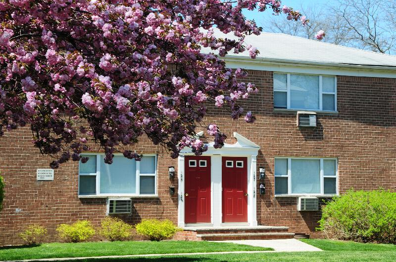Cloverleaf Gardens photo shows a brick exterior, red front door, green grass and a tree in bloom with pink flowers.