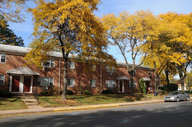 Cloverleaf Gardens photo of the exterior during fall, showing several large trees with yellow leaves. The front of an apartment building can be seen. It is brick with white trim and red front doors.