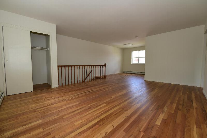 Photo of living area at Cloverleaf Gardens showing refinished hardwood floors and freshly painted walls.