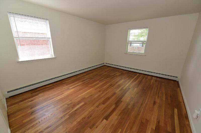 Photo of a bedroom at Cloverleaf Gardens showing refinished hardwood floors, freshly painted walls, and 2 windows that allow for fresh air and natural light.