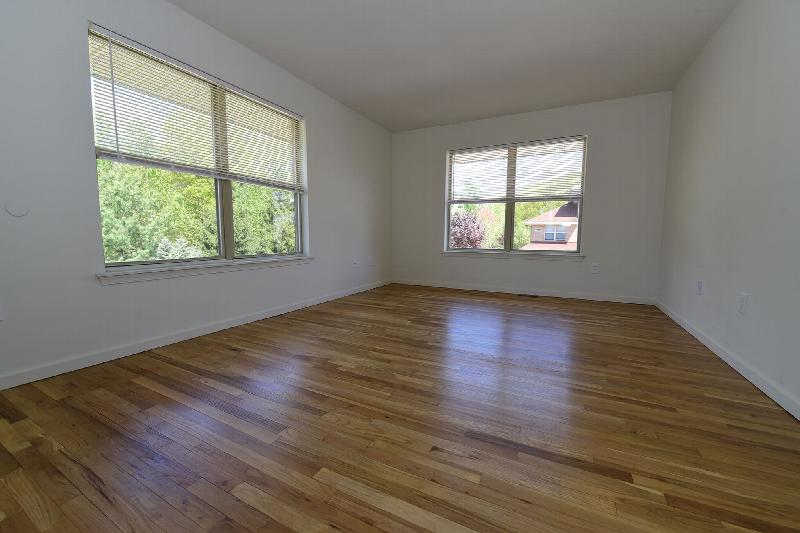 Image of a renovated bedroom at Evergreen Forest with refinished hardwood floors, newly painted walls, and two windows to allow for fresh air and natural light.