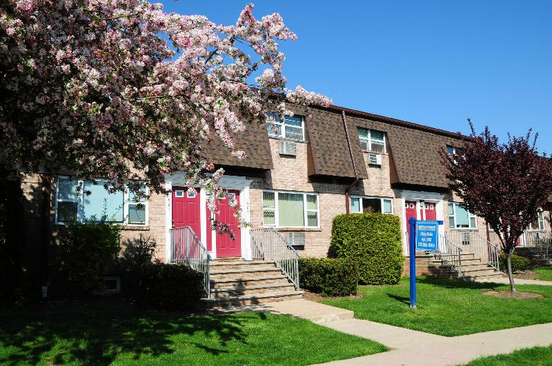 Woodbridge Village exterior photo shows a brick apartment building with red front doors and white trim. Green bushes and green grass line the front of the building and a flowering pink tree in the foreground.