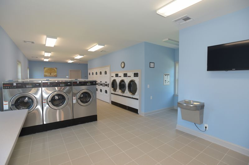 Woodbridge Gardens image of the laundry area shows multiple washer and dryers, a table top for folding laundry, a water fountain and a wall mounted TV